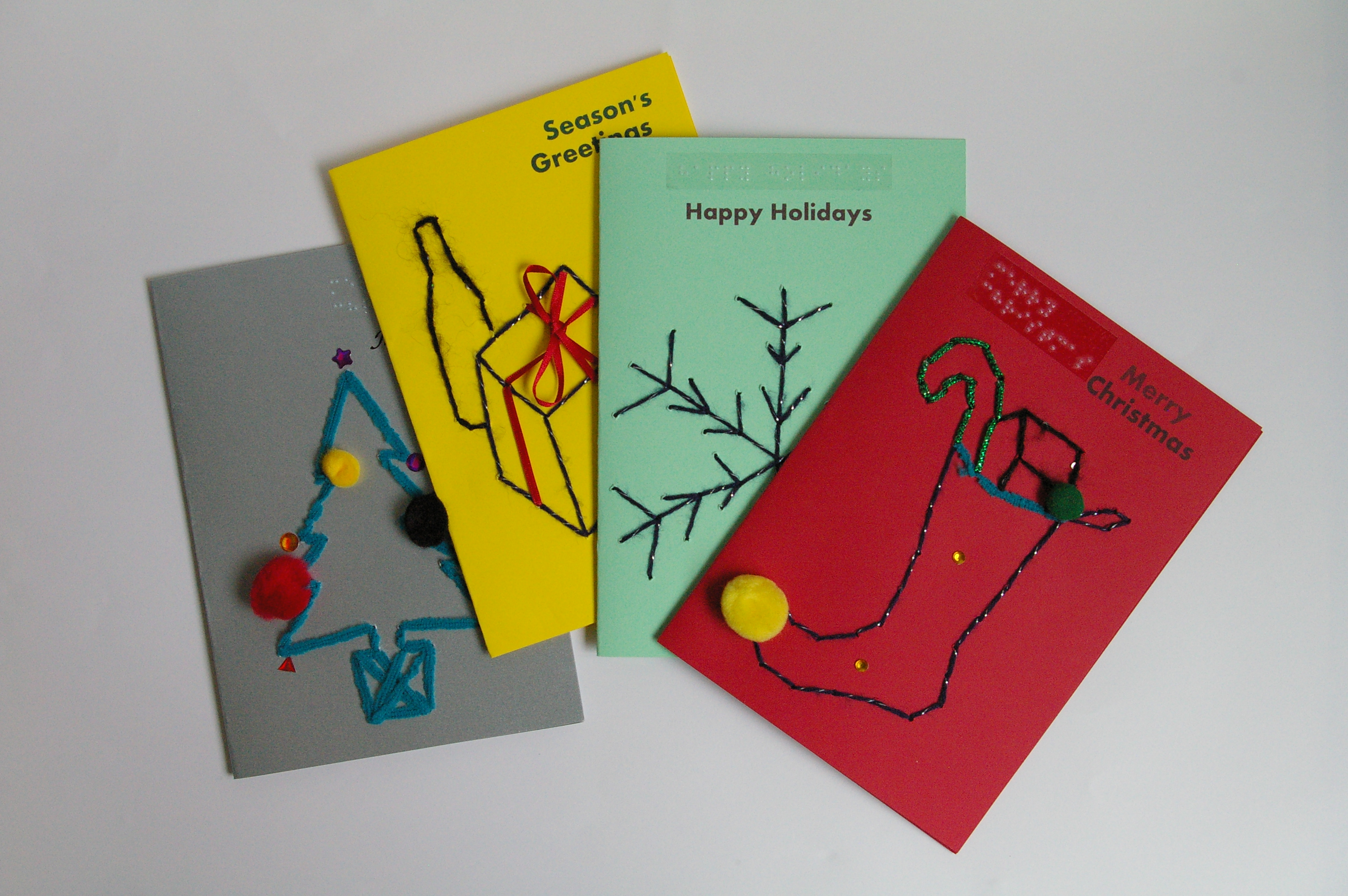 display of 4 brightly coloured christmas cards christmas tree presents snowflake and stocking - Christmas Card Packs