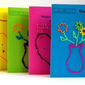 Four display of portrait style tactile scented Brailled greetings cards in multiple bright colours