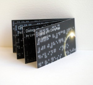 Fan display of Brailled business cards on white plinth