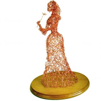 side view of wire lady with flower sculpture on round wooden base