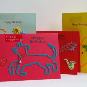 4 happy birthday card display includes dog playing with ball, large singular heart, vase with flowers and guitar music